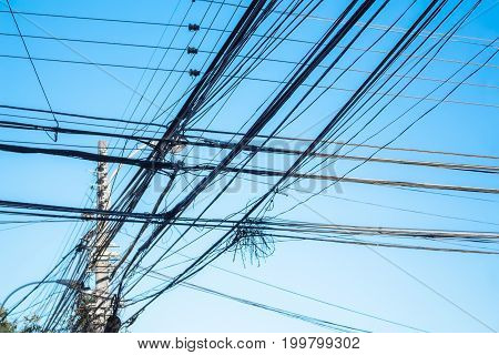 Bunch of electric wires on the pole on the sky background