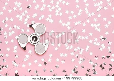 Silvery spinner on a pink background with stars. The concept of trend toys dreams fashion