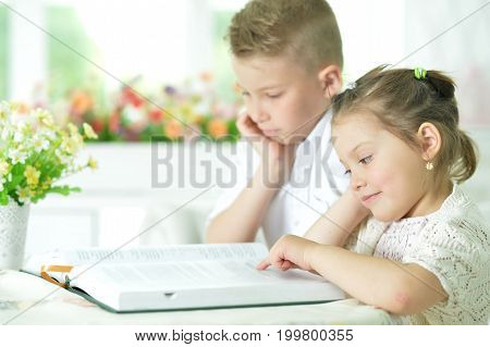 children sitting at table and reading interesting book