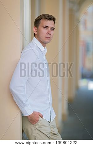 A portrait of an attractive guy with a focused expression leaning on the wall on a blurred street background. A successful student with hands on hips in summer clothes: light gray shirt and breeches.