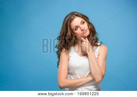The young woman's portrait with sad emotions at studio Presenting something