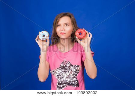 beautiful young funny girl with donuts on blue background. Unhealthy diet, junk food, party and celebration concept.