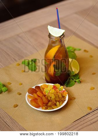 A table in a cafe with a plate of raisins and dried apricots, a moist bottle of a cool cocktail, green leaves of mint and slices of lime on a wooden blurred background.