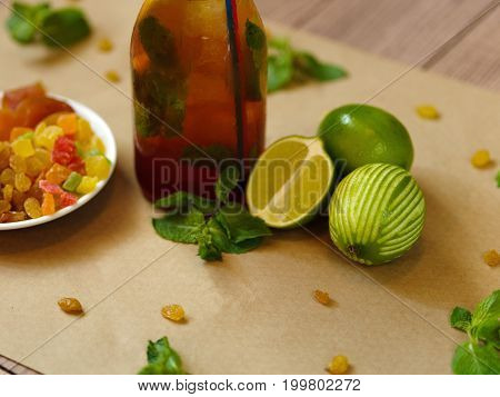 A wooden table with a plate of raisins and orange dried apricots, a wet bottle of a refreshing cool cocktail, green mint leaves and juicy lime on a light blurred background, close-up.