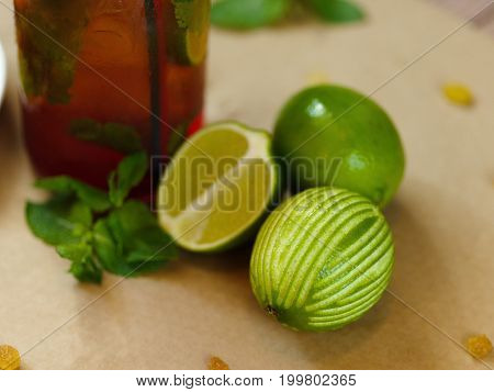 Close-up of a wooden table with aromatic green lime, a wet bottle of a cool cocktail, green sappy mint leaves and little raisins on a light blurred background. Summer composition.