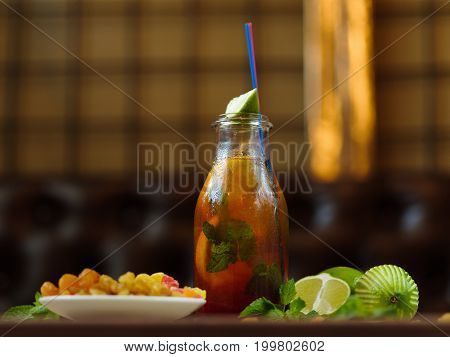 A table in a cafe with a plate of raisins and dried apricots, fragrant slices of green lime and a bottle of cool tea and mint leaves on a blurred background.