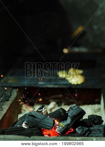 Close-up of grilling process. Glowing firewood next to grilled chicken. Black burning logs on a blurred dark background. Outdoors, nature, cooking concept. Copy space.