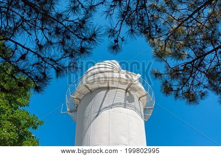 Open dome tower solar telescope through the branches of coniferous trees