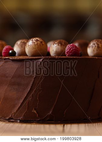 A light wooden table with appetizing chocolate pie sprinkled with cocoa and decorated with raspberries and black currants on a brown blurred background, close-up.