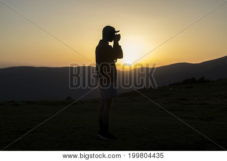 Silhouette of man which taking photo in the mountians