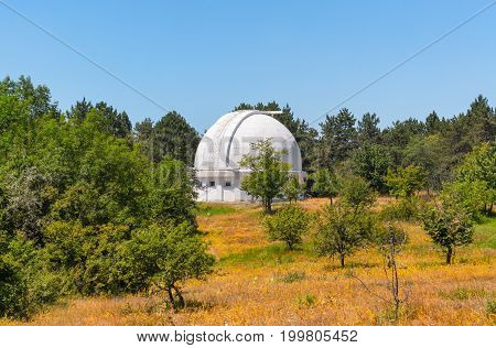 Telescope with a closed dome surrounded by trees. Coronograph in Observatory