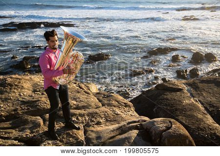 Musician play to musical instrument Tuba on romantic rocky sea shore.