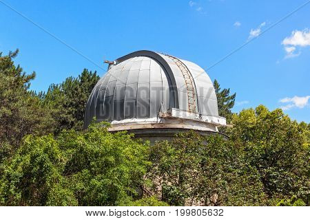 Closed dome of the old telescope in the observatory is among the crowns of trees.