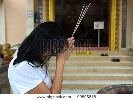 Asian woman praying for good luck in the temple
