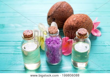 Organic spa products. Bottles with coconut oil coconuts and sea salt on bright wooden background. Selective focus