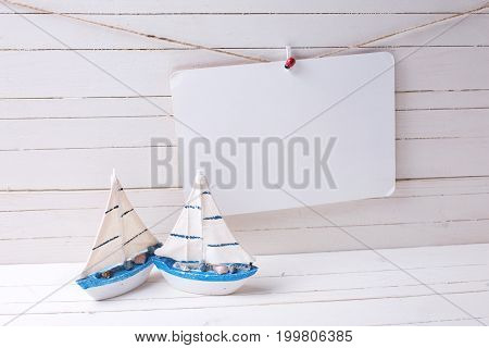 Decorative wooden toys sailing boats and empty tag on clothes line on wooden background. Selective focus. Place for text.