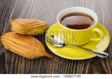 Cup With Tea, Teaspoon And Two Eclairs On Dark Table