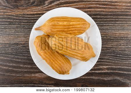 Three Eclairs In White Plate On Dark Wooden Table