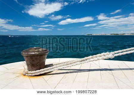 Iron bollard with attached hawser on quay in port in Zadar in Croatia.