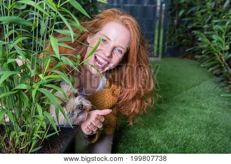 Beautiful red-haired woman plays with her dog in the garden