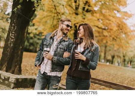 Young Couple Walking With Coffee Cups In The Autumn Park