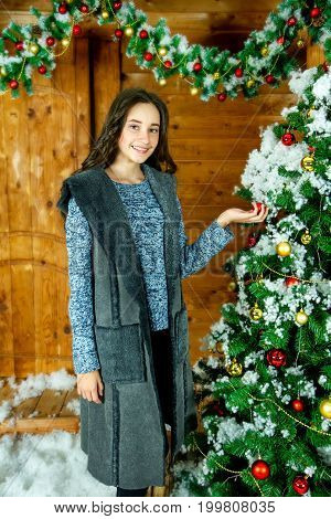Attractive young woman decorates the Christmas tree.