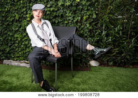 young red-haired woman dressed as a man on a chair in the garden