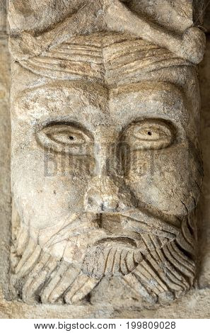 MONTMAJOUR FRANCE - JUNE 26 2017: Romanesque Carving of a Strange Head or Face (c12th) Capital in Cloisters of Montmajour Abbey near Arles Provence France