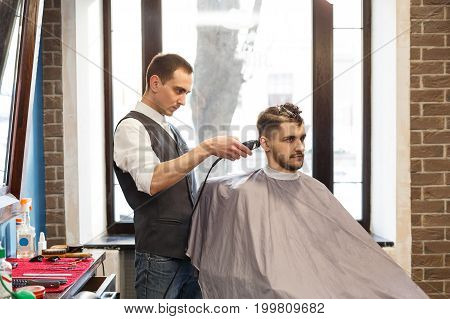Barber make beard haircut with trimmer hair clipper in barbershop. Hairstyle in barbershop.
