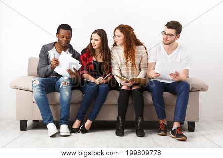 Diverse young students preparing for exam, sitting on sofa in living room and studying, studio shot