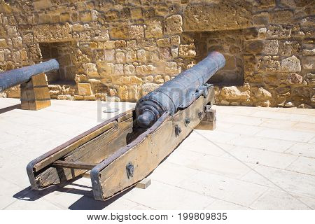 Antique cannons in the castle. Large heavy guns. Old medieval black iron cannon. Vintage Weapons