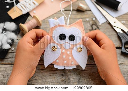 Small child holds a felt owl ornament in his hands. Child made Christmas owl ornament from felt. Sewing supplies and tools on an old wooden table. Easy kids sewing crafts for Christmas. Closeup