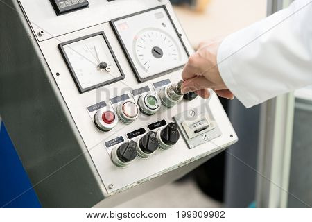 Close-up of the hand of a woman wearing white lab coat while turning on an industrial machine, with mechanical key-operated switch during work in a factory