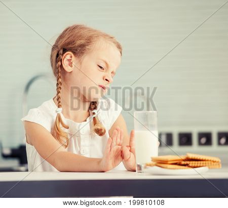 Child looks with disgust for food. Poor Appetite. Little girl does not like milk