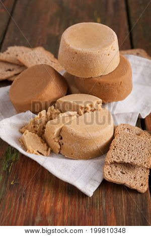 Norwegian homemade brown cheese brunost with crackers or crispbread on wooden desk, close-up, selective focus, vertical