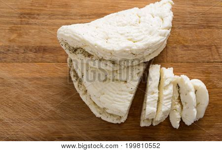 Fresh homemade halloumi or cheese paneer with herbs on wooden board in kitchen, close-up, shallow depth of field, top view