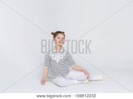 Portrait of naughty astonished girl sitting on the floor at white studio background. Child in casual clothes posing on camera, copy space