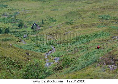 Walker In Scottish Highlands Descending To Shenavall Bothy