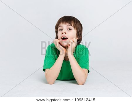 Portrait of surprised boy lying on the floor at white studio background. Kid in casual bright clothes posing on camera, copy space