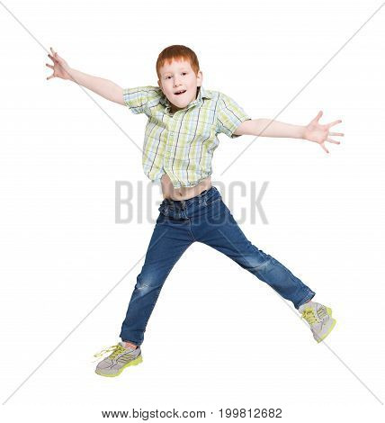Jumping happy boy on white isolated background. Casual redhead kid bouncing with raised hands at studio. Active life and happy childhood concept