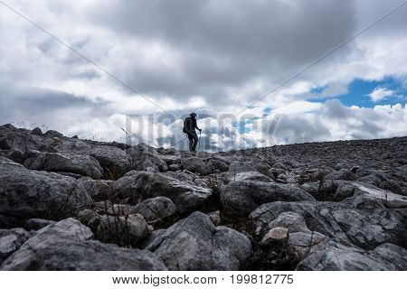Walker Silhouette On Rock Field On  Scottish Highland Munro