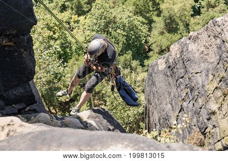 Lilienstein Germany - August 14 2017. A rock climber going down a steep mountain with a rope. Climber in Saxon Switzerland (Lilienstein mountain) Koenigstein Germany.