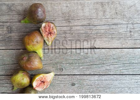 Ripe green and brown figs located on the left on the wooden table