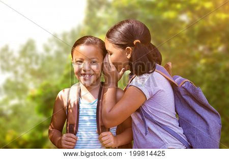 Girl with backpack whispering in friend ear against trees in the forest