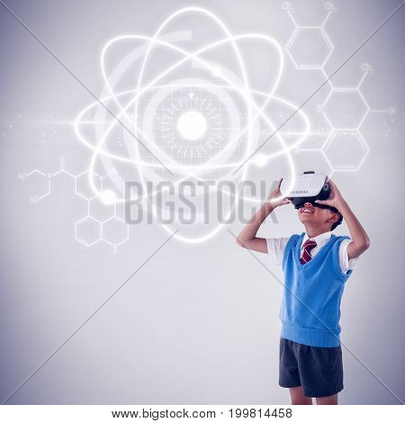 Atomic structure against black background against schoolboy using virtual reality headset