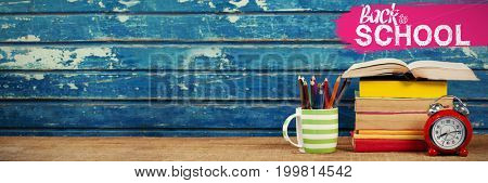 back to school against stacked books with alarm clock and pencils on table