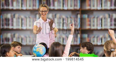 Students raising hands while teacher teaching against library shelf