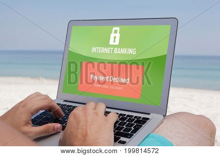 Internet banking text on green display against man using laptop while resting at beach