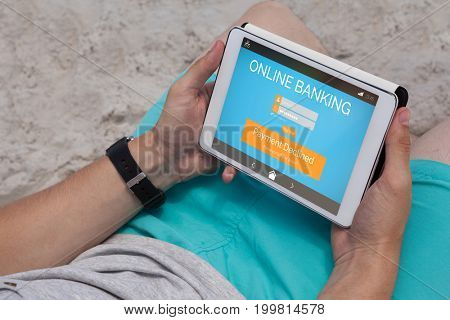 Online banking text on phone display against man using digital tablet on the beach