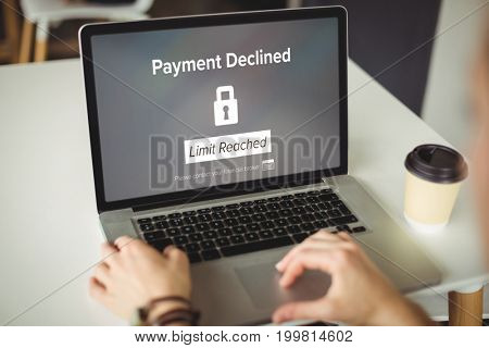 Payment declined text on black display against cropped hands of woman using laptop